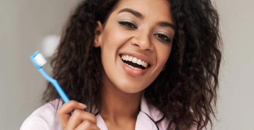 lady-sitting-on-bed-with-toothbrush-in-hand-and-M2E86QA-1.jpg